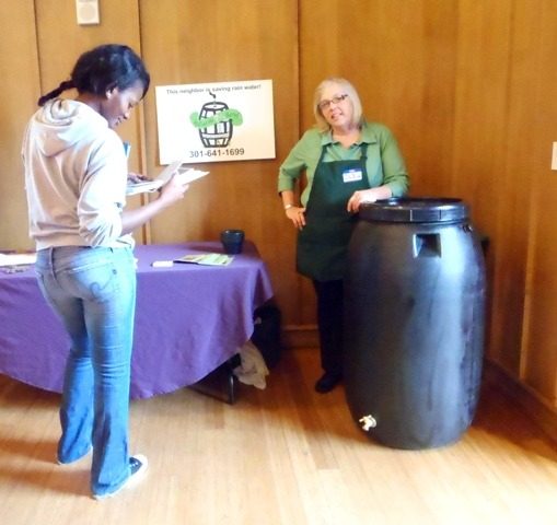 Image of woman learning about rain barrels.