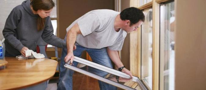 Image of homeowners installing energy efficient windows.