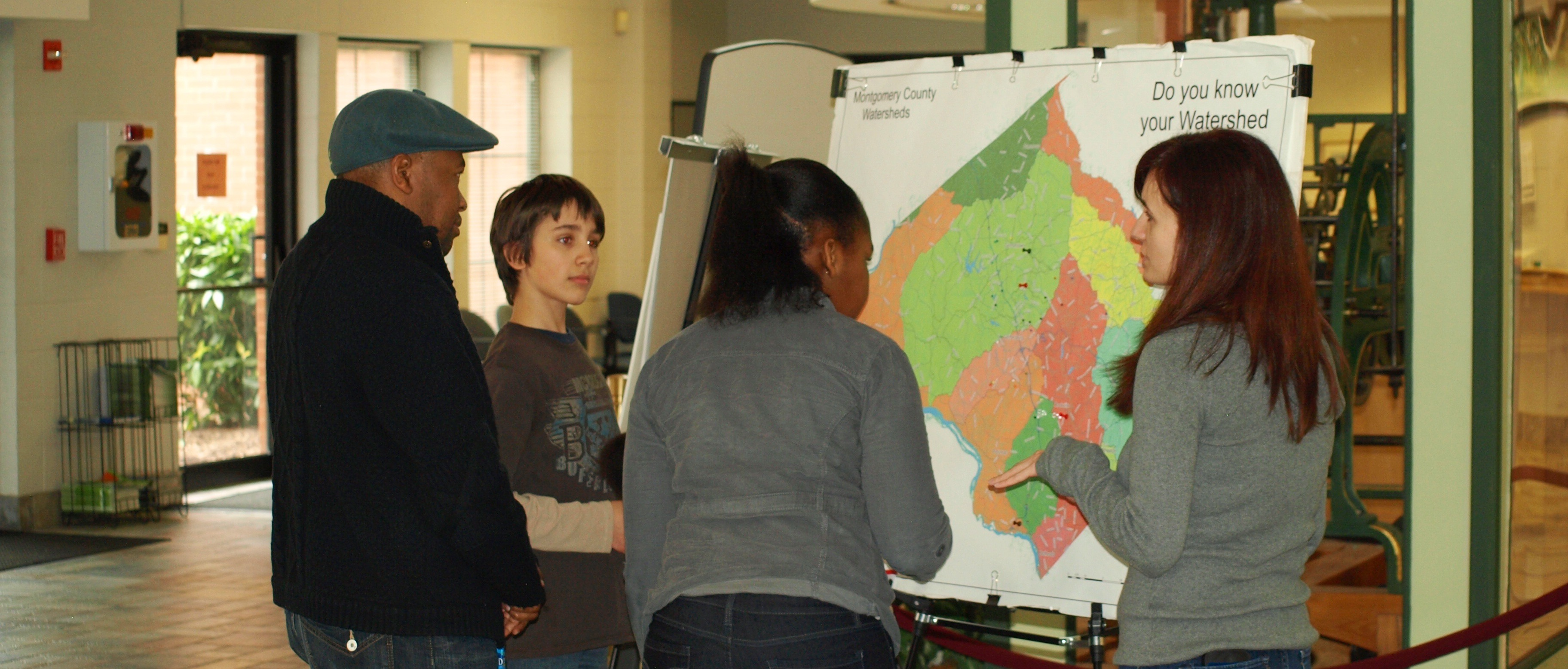 Photo of families with a map of Montgomery County watersheds at the H2O Summit
