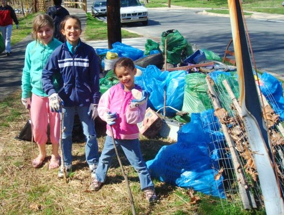 Photo of girls after a trash pickup. They have piles of trash collected behind them.
