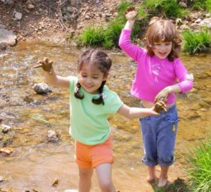Photo of two children playing in a creek during the Montgomery County Department of Environmental Protection's staff trash pick-up event.