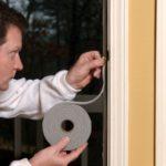 Image of man installing home sealing around windows.