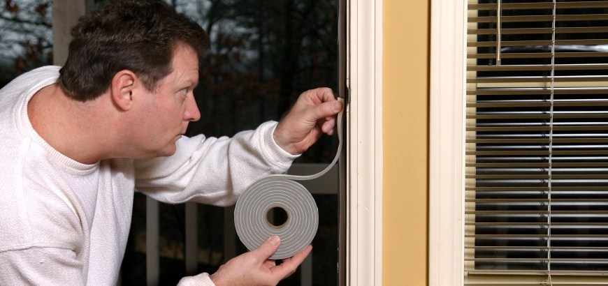 Image of man installing home sealing around windows.