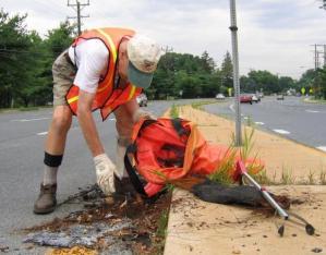 Photo of a volunteer picking up litter along a roadside.