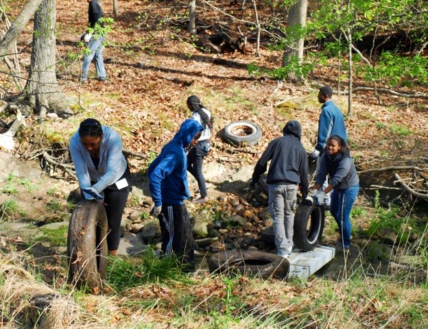 Image of volunteers removing tires from a park.