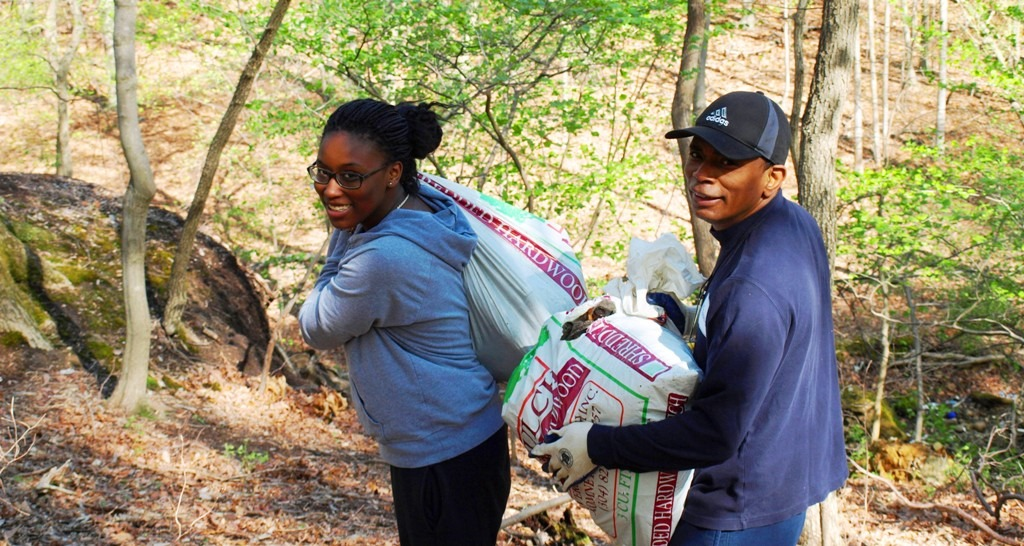 Image of two volunteers carrying bags of trash during the White Oak Earth Day Cleanup