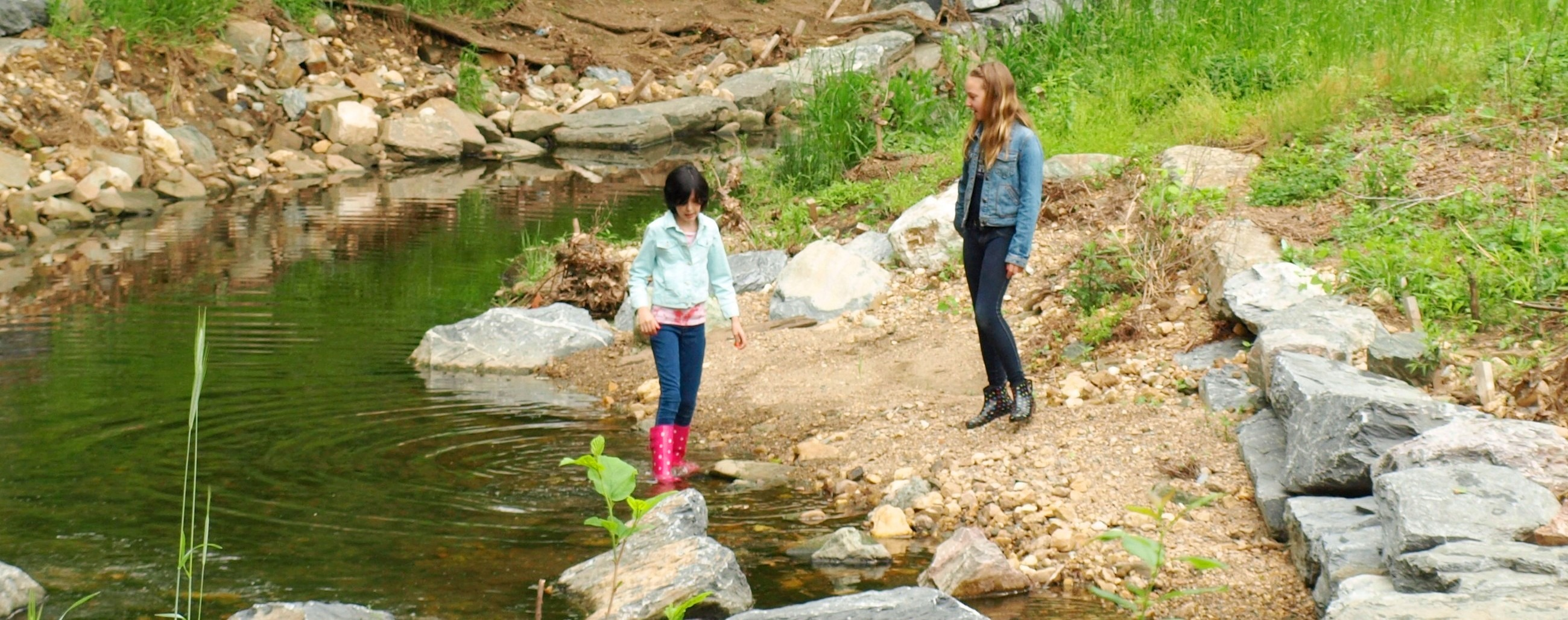 Image of two girls playing by Booze Creek.