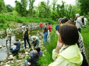 Image of DEP staff member talking to a crowd of about 30 about the creek restoration.