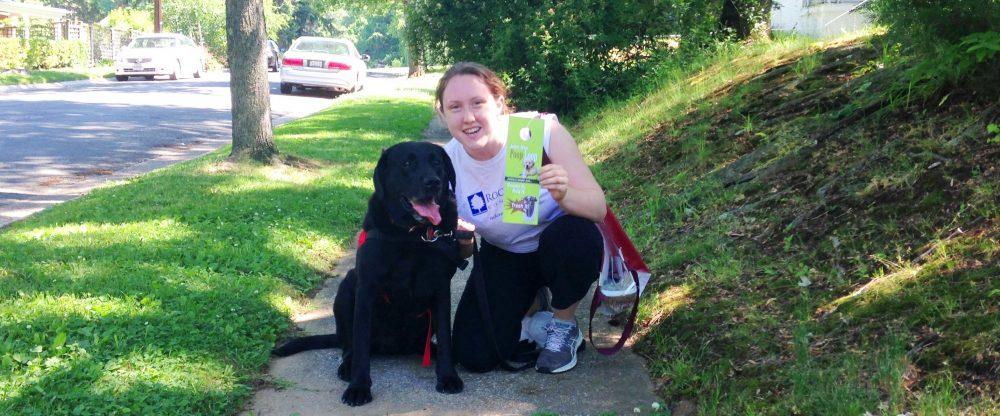 Image of Karen from Rock Creek Conservancy and her dog Milo with the poop loop sign.