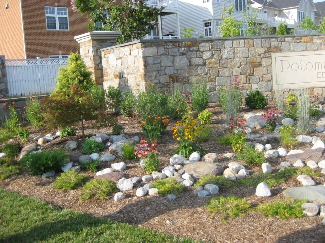 Image of the entrance to a community. The entrance has a rain garden.