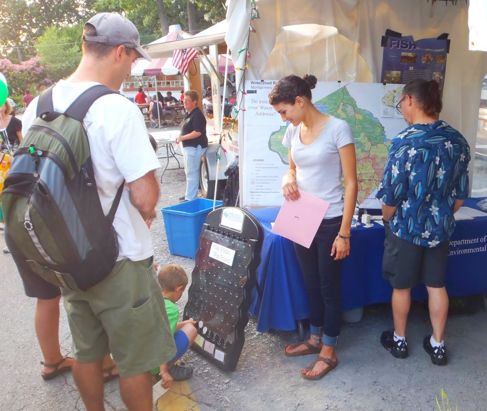 Image of Department of Environmental Protection volunteer teaching a family about their waterways.