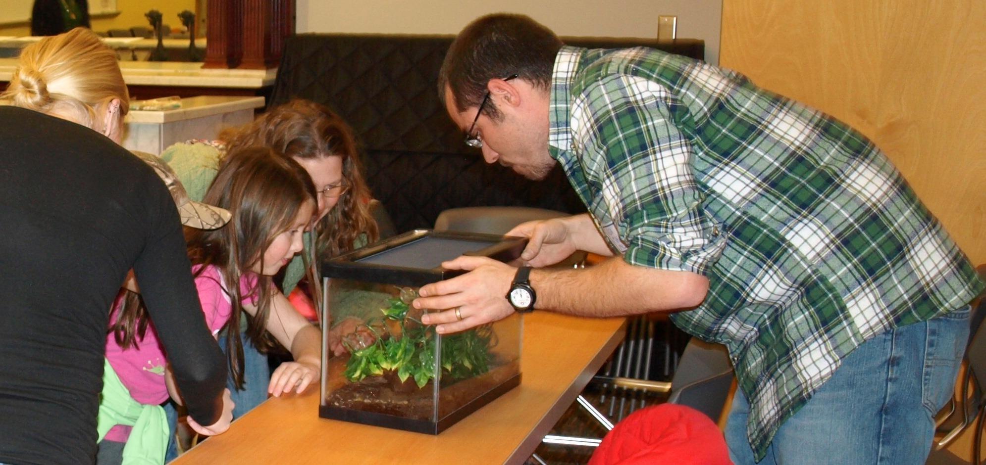 Image of DEP staff biologist showing kids a gray treefrog.