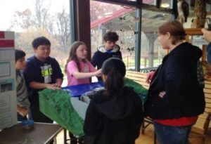 Image of Cabin John Middle School students presenting their research at a community event.