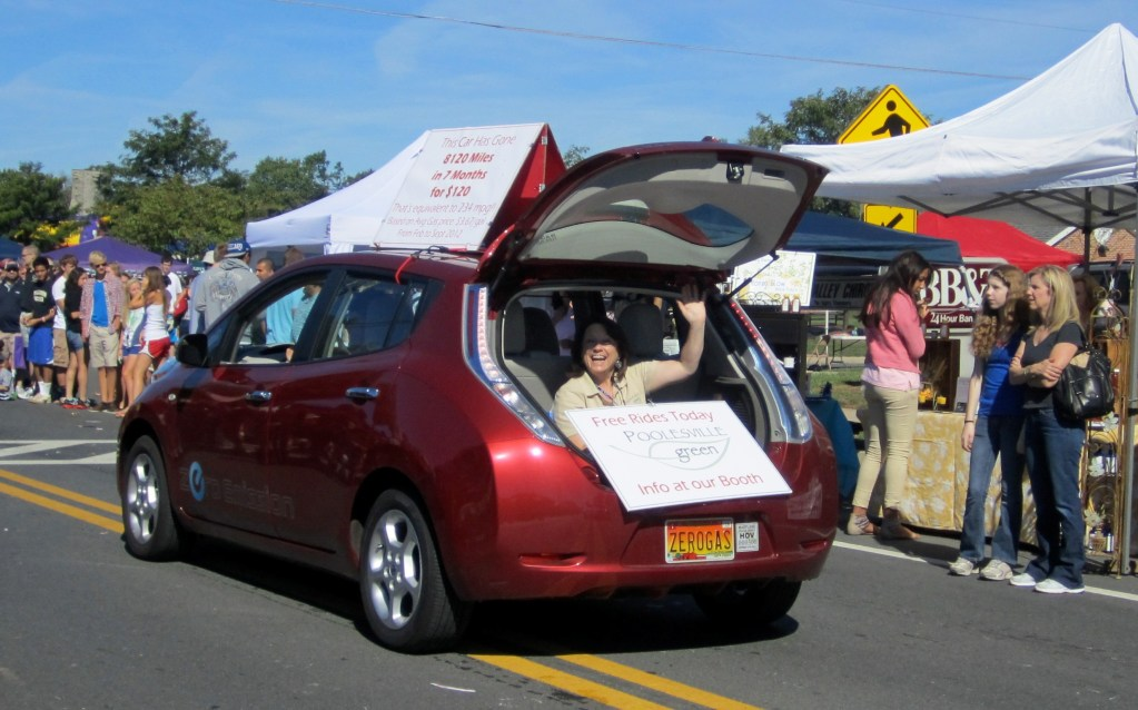 A woman rides in back of an electric vehicle in the Poolesville Day Parade