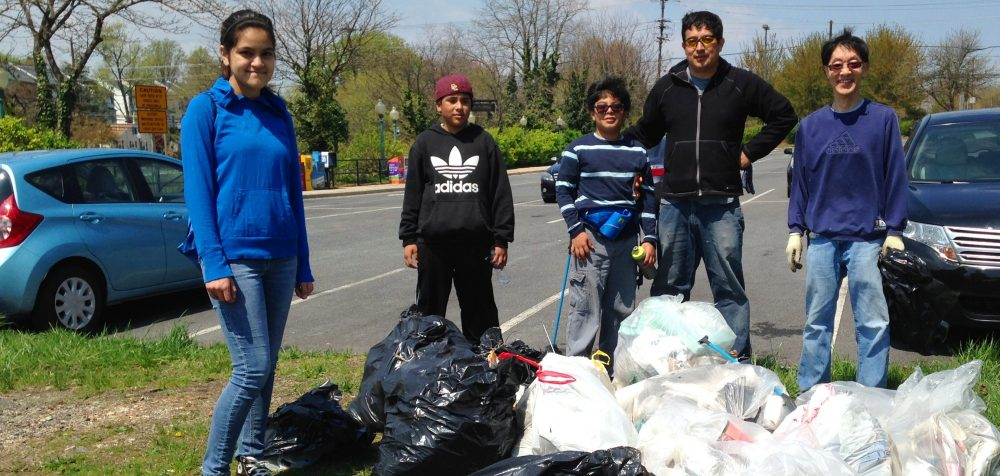 Five volunteers standing next to all the trash they picked up from a stormwater facility.