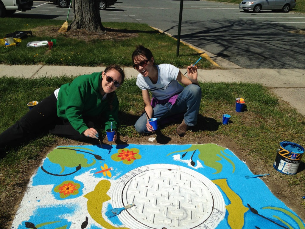 Two volunteers painting art onto a storm drain