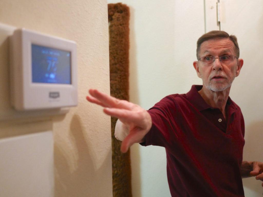 Joe Halpin points to his smart thermostat