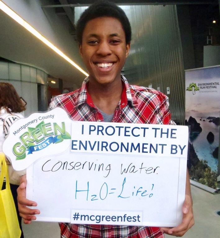 "A man holding an ""I protect the environment by"" sign with ""Conserving water H20=Life"" written in. This picture was taken at the Montgomery County Green Fest"