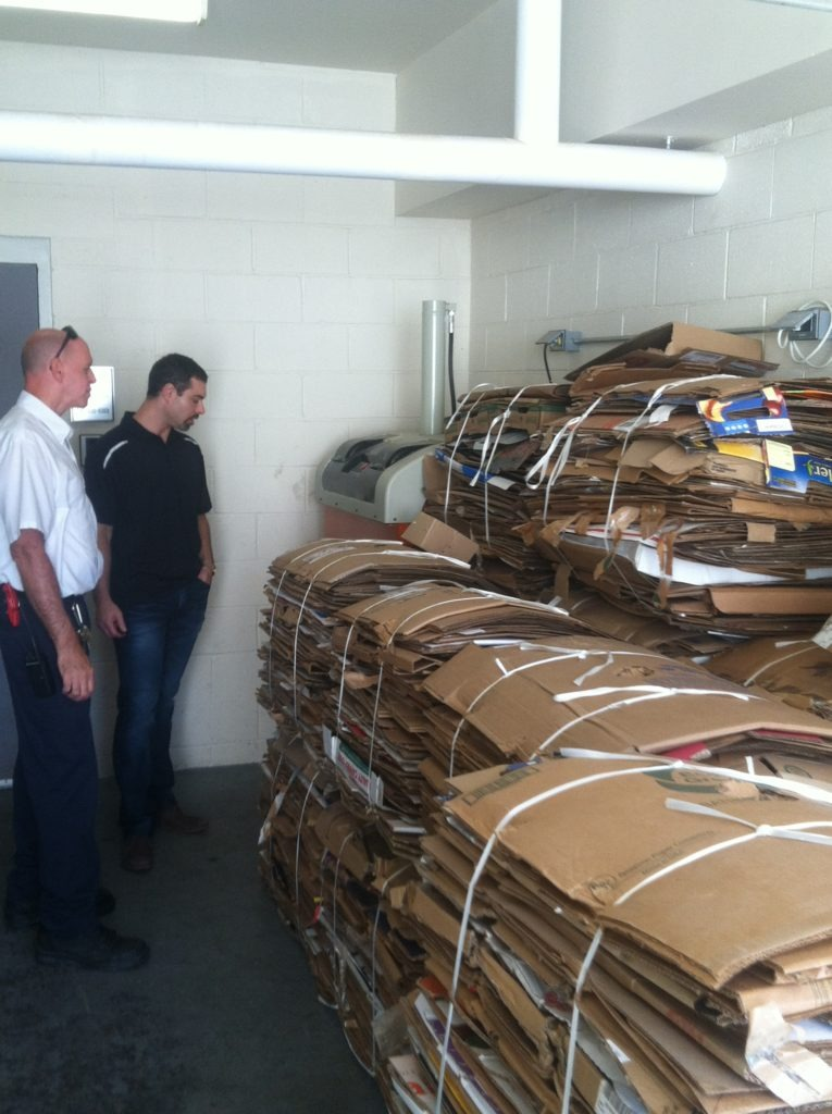 Employees standing next to stacks of cardboard