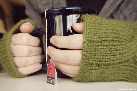 Hands wrapped in long sweater, holding a hot cup of tea, photo courtesy of Flickr user lisaclarke
