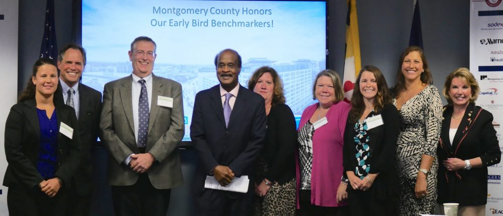 Business owners stand with the County Executive to receive their early benchmarking awards