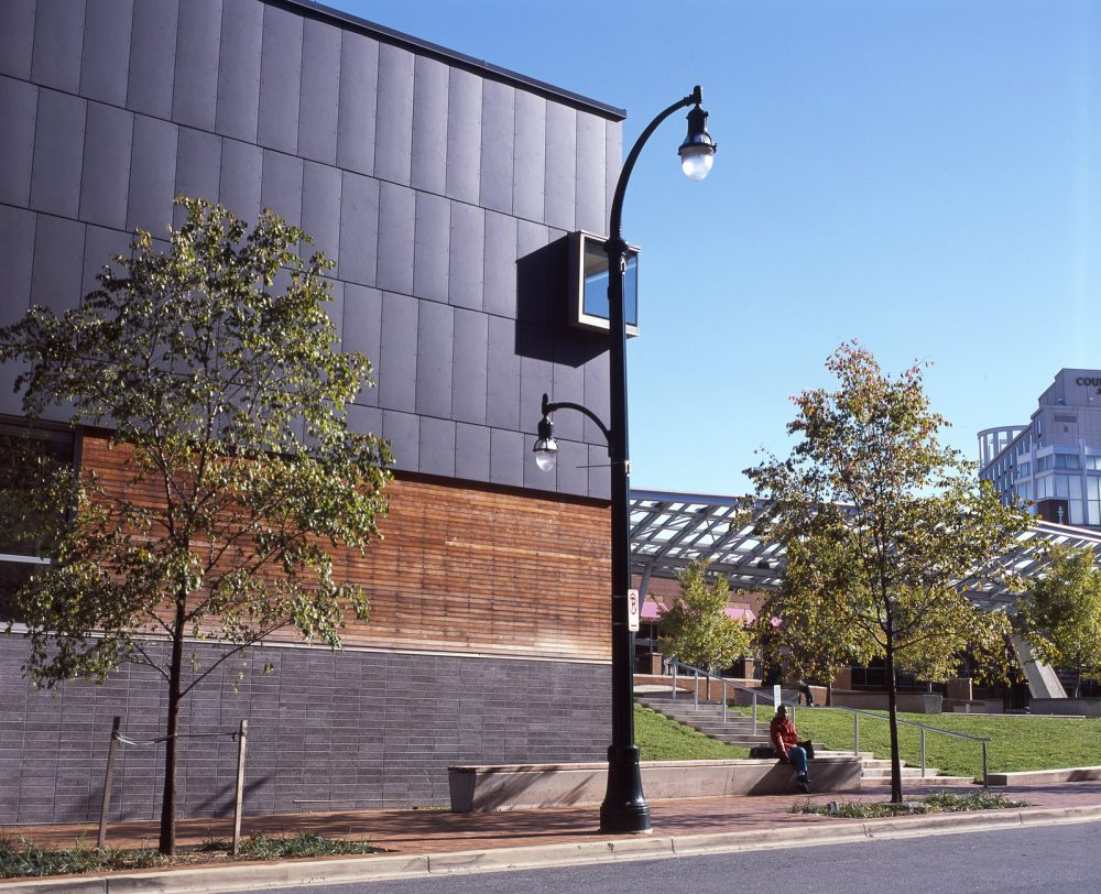An image of the side of the exterior of the Silver Spring Civic Building, with a person sitting on the steps.