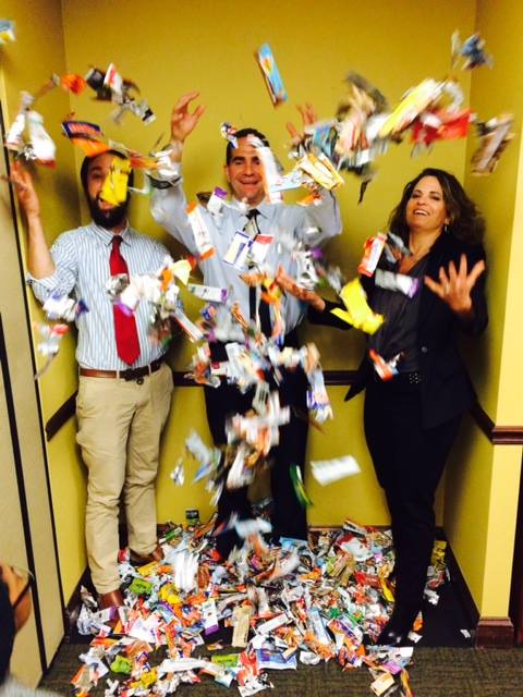 Employees toss energy bar wrappers in the air