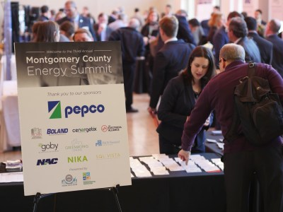 Energy Summit sign placed next to patrons checking in at the front desk