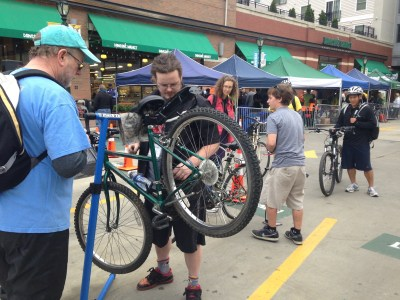 Attendees of Bike to Work Day stand around a man whose bike is suspended and being worked on