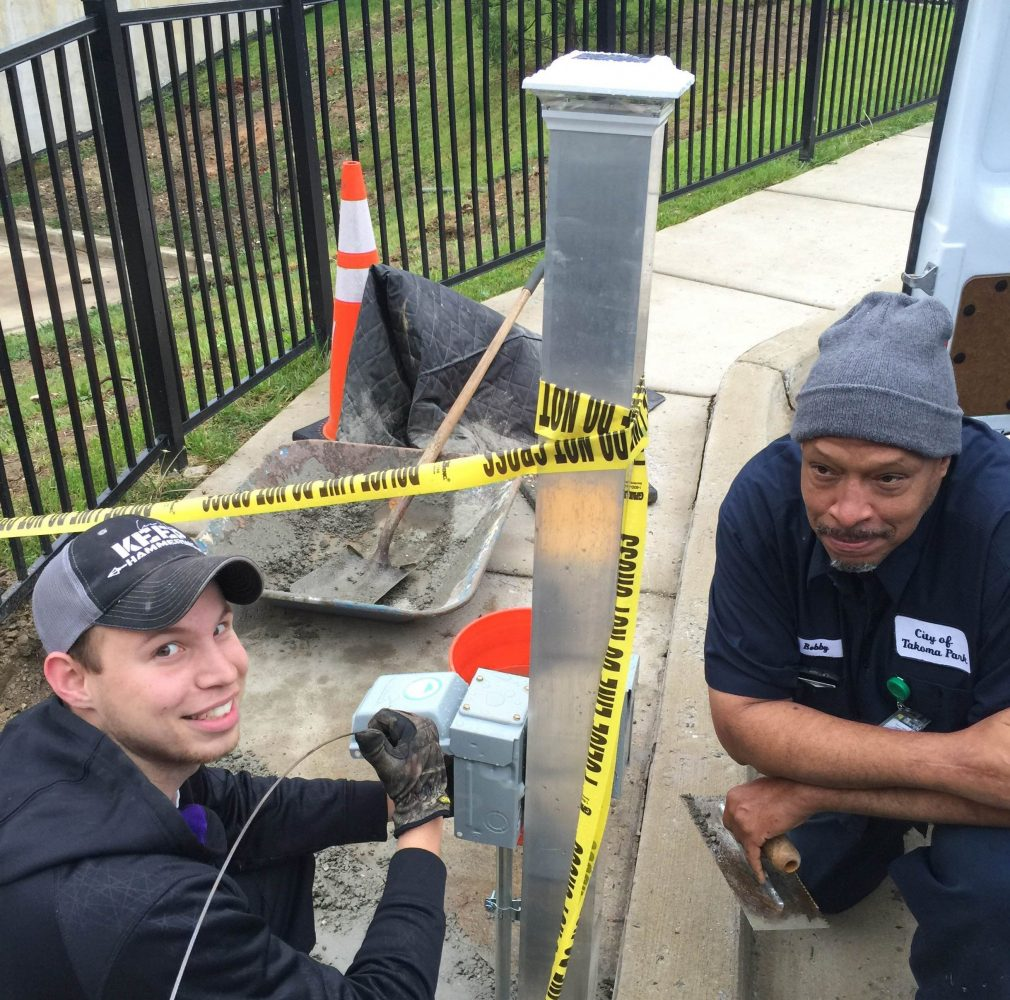 Two men install an electric vehicle charging station