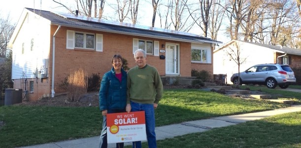 "A man and a woman stand in front of their home, next to a sign that reads ""We Went Solar!"""