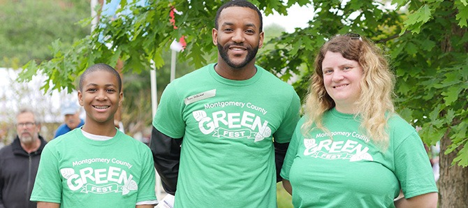 A young boy, a man, and a woman smile for the camera, wearing GreenFest tshirts