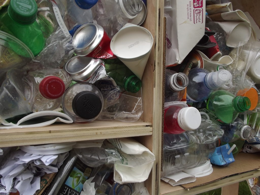 A close up of recyclables in the wooden structure, including bottles, cans, and paper