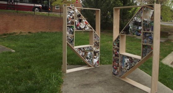 2 wooden sculptures displaying trash and recyclables