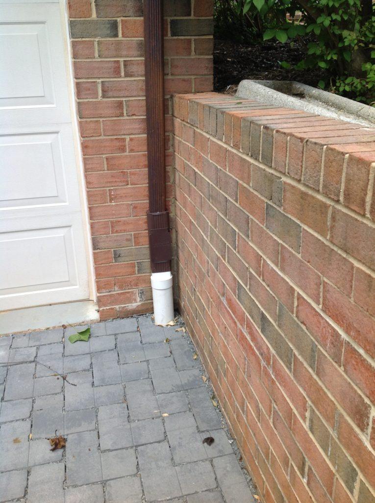 a downspout drains under permeable pavers