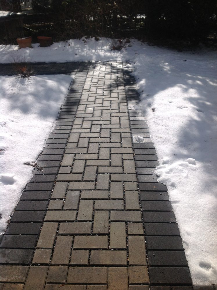 A clear permeable paver path, surrounded by snow