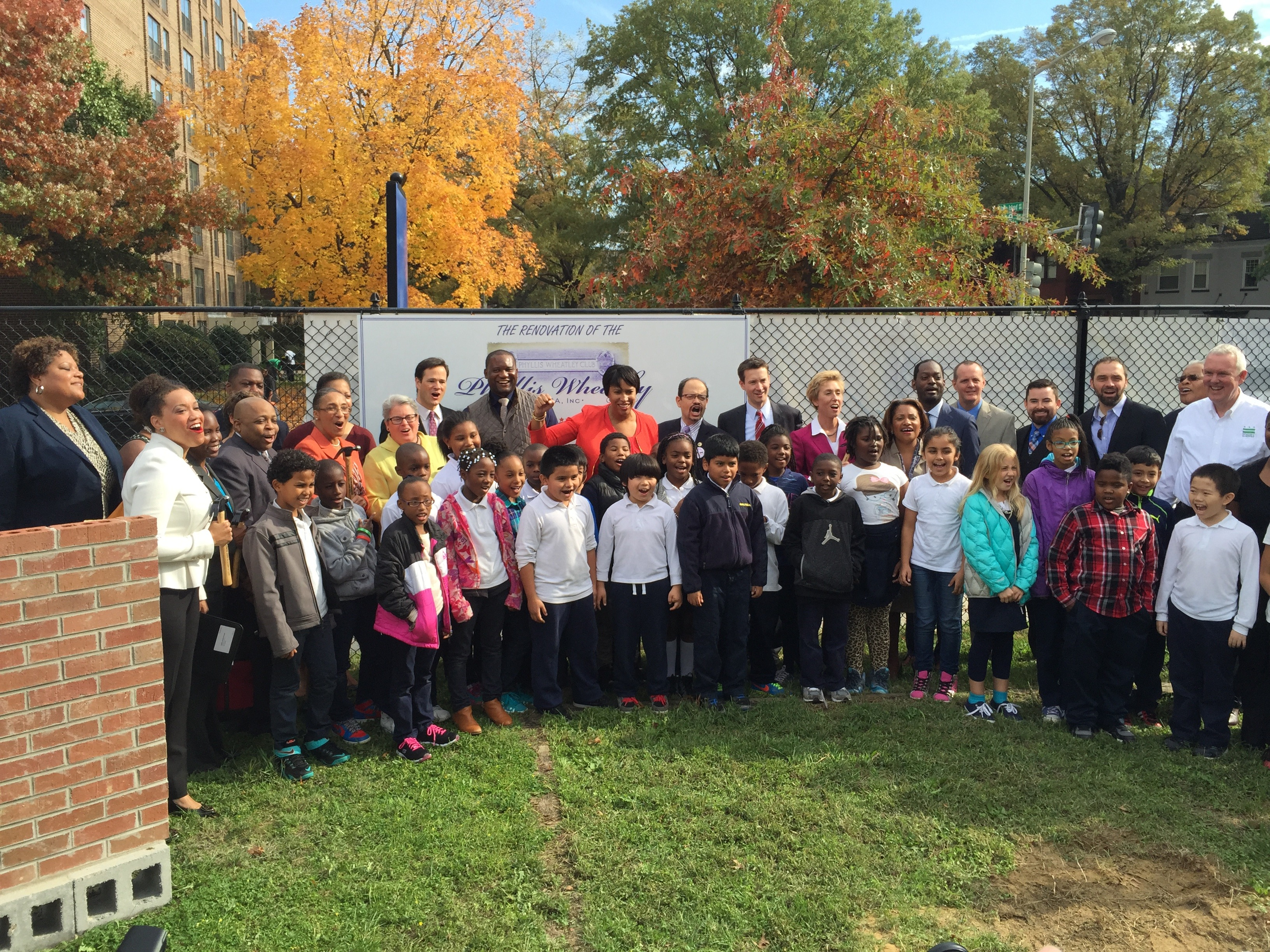 Mayor Muriel Bowser stands with a group of smiling adults and children
