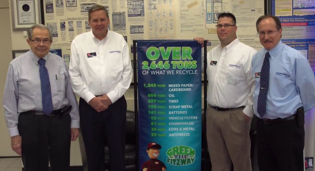 Senior members of Fitzgerald Auto Mall's Green Team, including Founder Jack Fitzgerald (far left),in front of a banner celebrating their extraordinary recycling efforts.