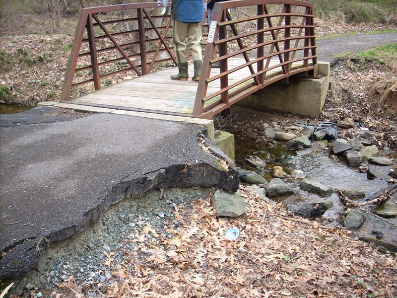 <strong>Pre-Restoration:</strong> Downstream scour, or erosion, on M-NCPPC walking path bridge. Following increased development in the watershed, the opening under the original bridge was no longer large enough to carry stream flow during heavy rain storms. Water would overtop the banks and flow around the bridge, causing erosion and damage to the asphalt pathway and threatening the bridge structure.