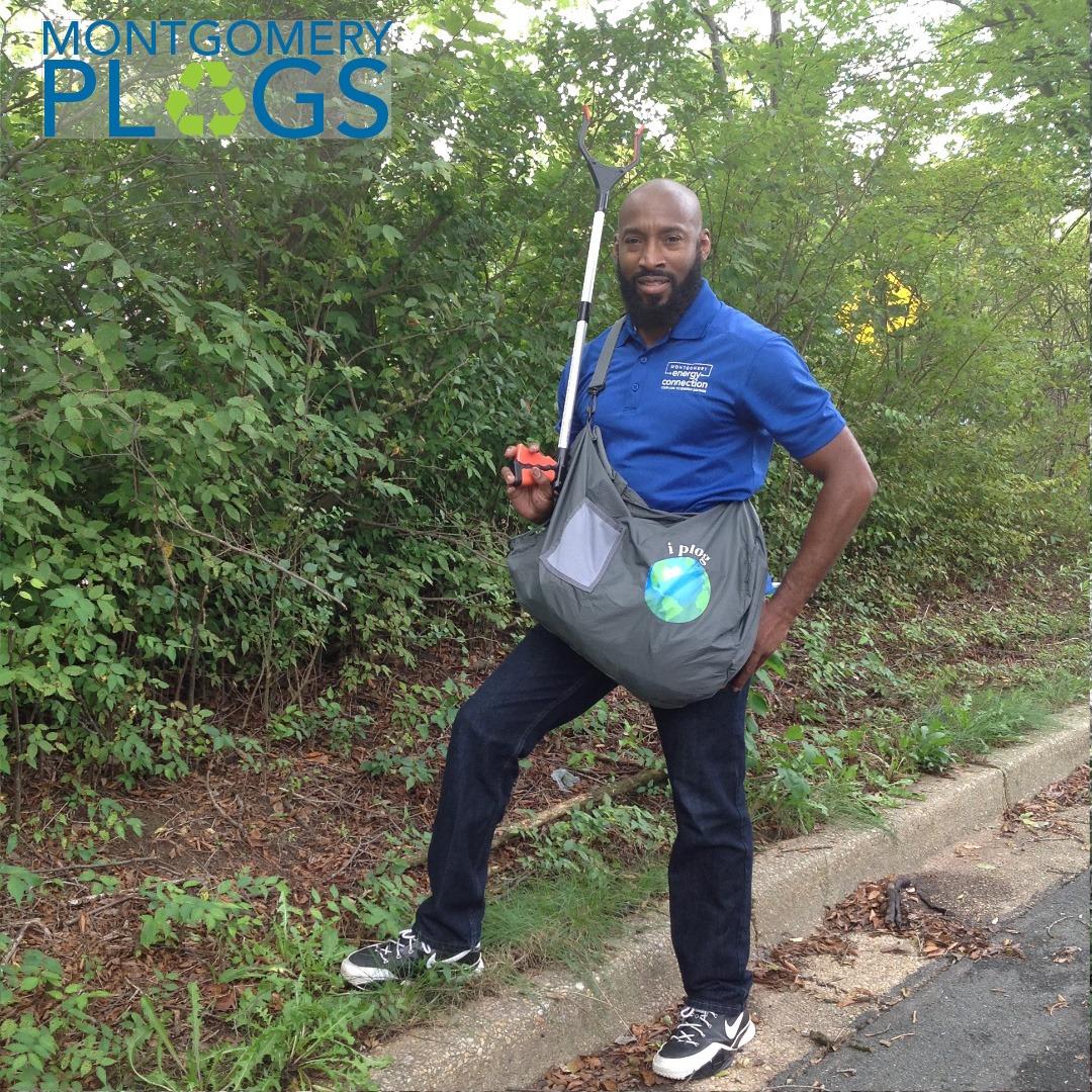 volunteer holing a trash pick-up stick and wearing a plogging bag